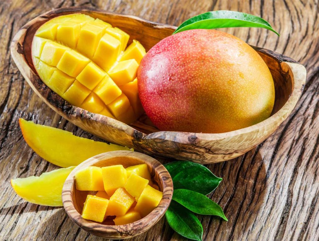 Mangofrüchte und Mangowürfel auf dem Holztisch. Dürfen Hunde diese leckere Frucht essen?